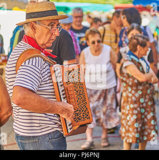 Saint Felicien, Ardeche department of the Rhone Alps and an accordion player entertains people at the cheese festival. - Stock Photo