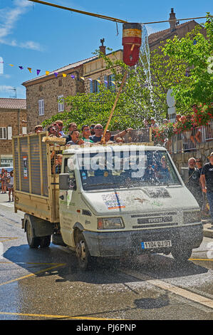 Saint Felicien and a white open back van passing under a water bucket as part of the festival of the goat and cheese - Stock Photo