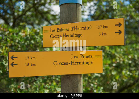 Yellow fingerpost signs on a timber post on the hillside above Tain L'Hermitage in the Drome department, Rhone Alps region, France - Stock Photo