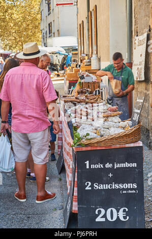 Market trader selling meats during the market at Lamastre, Ardeche, Rhone Alps, France - Stock Photo