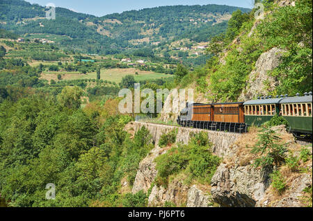 The steam train 'Train de L'Ardeche' descends through the Gorge de Doux on its way back from Lamastre to Tournon sur Rhone, in the Ardeche department - Stock Photo
