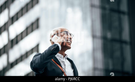 Man in formal clothes wearing office bag walking on street while talking on mobile phone. Smiling businessman talking over cell phone while commuting  - Stock Photo