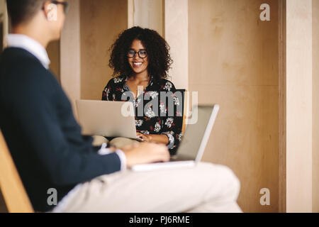 Smiling woman entrepreneur working on laptop sitting on chair with a businessman sitting in front. Office colleagues working on laptops sitting on cha - Stock Photo