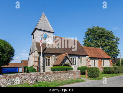 Roadside view of Church of St Thomas of Canterbury and its flint churchyard wall in East Clandon, a small village in Surrey near Guildford, SE England - Stock Photo