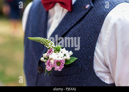 Pink flowers boutonniere flower groom wedding coat with vest. - Stock Photo