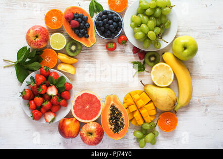 Rainbow color fruits arranged in a circle, strawberries, blueberries, mango, orange, grapefruit, banana, apple, grapes, kiwis on the white background, - Stock Photo