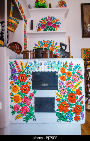 Zalipie, Poland, August 19, 2018:   Colourful room in the log house in the village Zalipie, Poland. It is known for a local custom of painting the cot - Stock Photo
