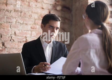 Serious HR manager interviewing young woman candidate - Stock Photo