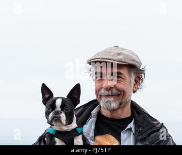 Close up of happy smiling senior man with dimples and a graybeard, wearing a cap, holding a cute boston terrier wearing a harness looking at the camer - Stock Photo