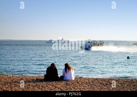 Two young ladies sitting on beach with a passenger hovercraft  in foreground and the cruise liner Queen Victoria sailing past Spithead Portsmouth UK - Stock Photo