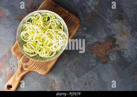 Spiralized zucchini pasta on the grey stone background, selective focus, top view, copy space for text - Stock Photo