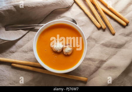 Flat-lay of fall warming pumpkin cream soup with croutons over tablecloth background Autumn vegetarian, vegan, healthy comfort food eating concept - Stock Photo