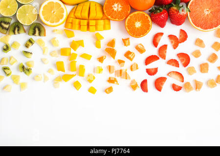 Top view of red, orange, yellow, green fruits with cut pieces on the white background; grapefruit, mango, strawberries, orange, lemon, kiwi - Stock Photo