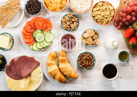 Top view of the healthy filling breakfast, ham, cheese, cereals, toast, nuts, jam, vegetables, croissants, selective focus - Stock Photo
