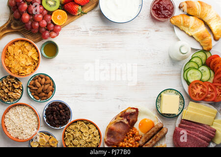 Top view of the healthy filling breakfast, eggs, sausages, bacon, beans, cheese, cereals, toast, nuts, jam, vegetables, croissants, frame, copy space, - Stock Photo