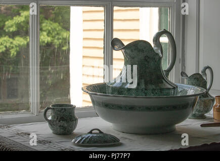 Antique pitcher and bowl from 1800s sitting on washstand, romantic vintage Victorian elegance - Stock Photo