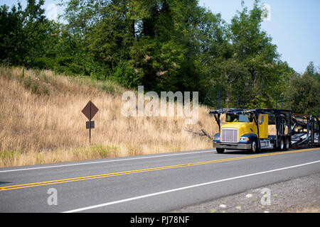 Specialized empty yellow big rig car hauler semi truck with two-tiered semi trailer going to load cars on winding road with hill and green trees - Stock Photo