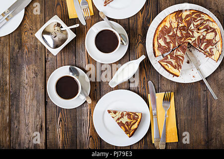 Chocolate cheesecake and coffee on wooden background. Cup coffee and cheesecake.Top view. Flat lay - Stock Photo