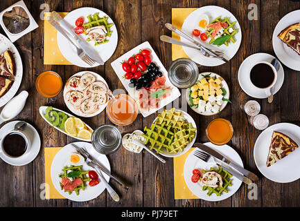 Breakfast food table. Festive brunch set, meal variety with spinach waffles, salmon, cheese, olives, chicken rolls and cheesecake. Top view. Flat lay - Stock Photo