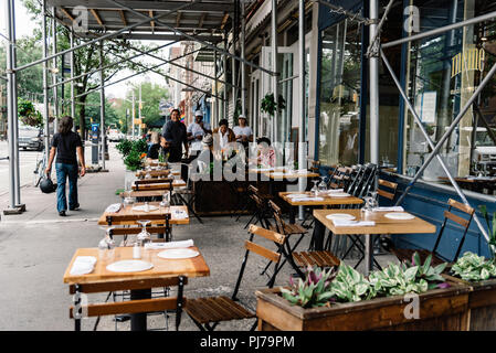 New York City, USA - June 22, 2018:  Sidewalk cafe with people enjoying in Greenwich Village - Stock Photo