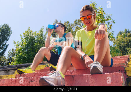 Runners resting taking a break drinking water after running outside - Stock Photo