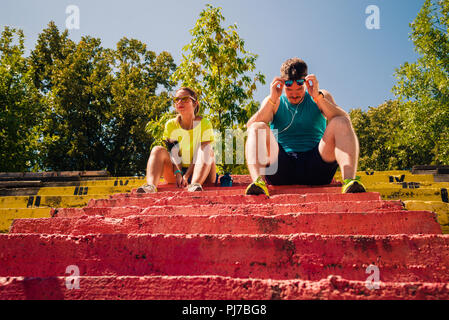 Runners in the city park resting after jogging and listening to music - Stock Photo