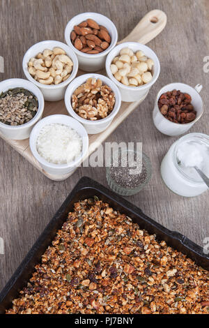 Grain free paleo granola: mixed nuts, seeds, raisins, coconut flakes, chia and coconut oil - Stock Photo