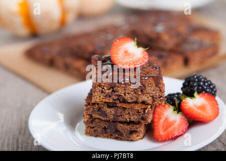 Healthy gluten free dairy dree paleo style  flourless  pumpkin brownies with chocolate chips, served with strawberries, selective focus - Stock Photo