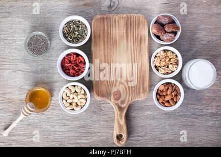 Grain free oat free paleo granola ingredients: mixed nuts, seeds, goji berries, chia, honey and coconut oil, selective focus - Stock Photo