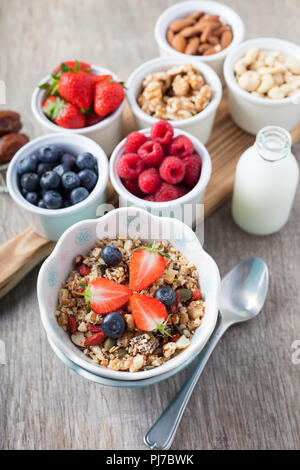 Paleo style breakfast: grain free oat free granola  with almond milk and with mixed nuts, and fresh berries, selective focus - Stock Photo