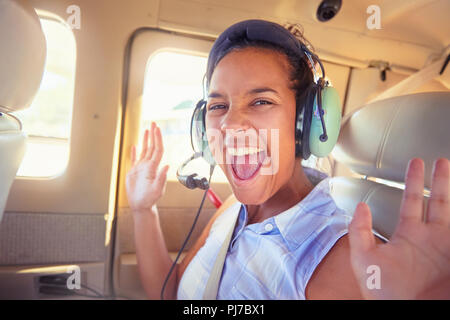 Portrait enthusiastic young woman with headphones riding in airplane - Stock Photo