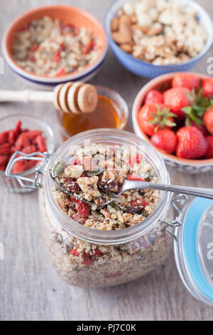 Grain free oat free paleo muesli, raw food: mixed nuts, seeds, goji berries, chia, honey and strawberries, selective focus - Stock Photo