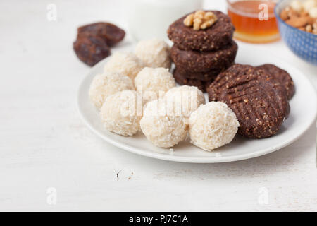 Raw vegan paleo style cookies selection, made with nuts, coconut oil, honey and dates, selective focus on closest macaroon - Stock Photo