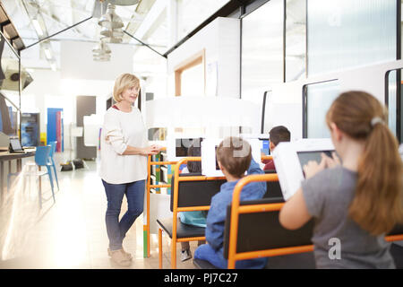 Teacher and students using touch screen computers - Stock Photo