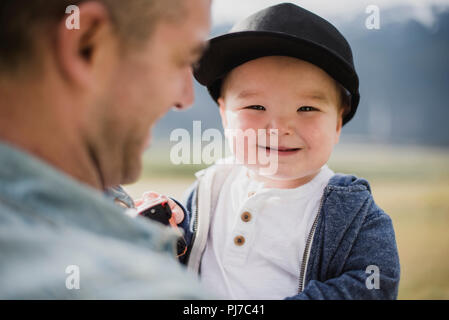 Portrait cute baby boy over father s shoulder - Stock Photo