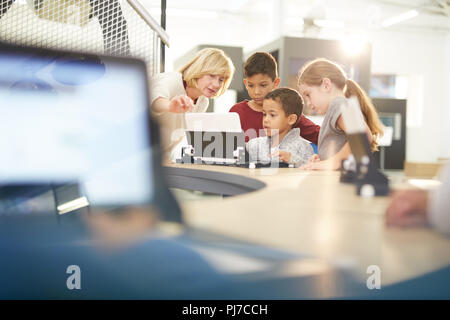 Teacher and students using laptop - Stock Photo