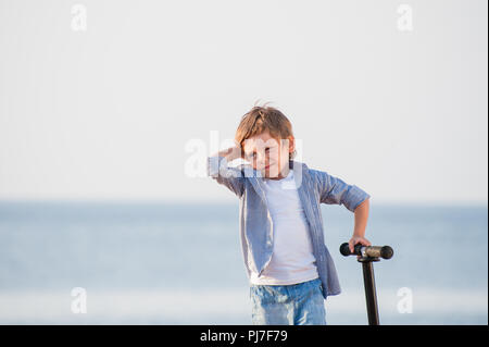 strange cute little boy with grimace on his face with scooter on sea autumn shore - Stock Photo