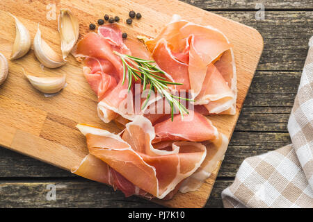 Italian prosciutto crudo or jamon on cutting board. - Stock Photo