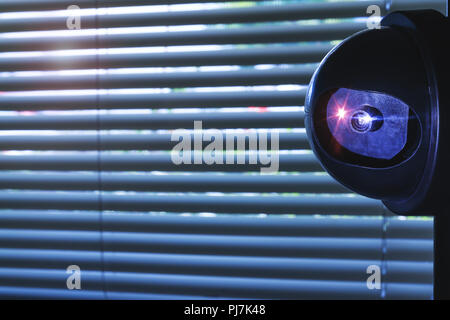 Security Camera inside of the office building or home room, in front of the window blinds. CCTV camera or surveillance system installed on wall. Priva - Stock Photo