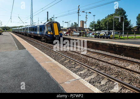 A Siemens Class 380 Desiro electric multiple-unit train (ScotRail run by Abellio) arriving at the halt in Dalry, North Ayrshire en route to Glasgow. - Stock Photo