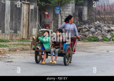 Ha Giang, Vietnam - March 18, 2018: Mother carrying two children on a manual truck in a remote rural area of northern Vietnam - Stock Photo