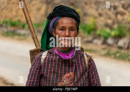 Ha Giang, Vietnam - March 18, 2018: Portrait of a woman from the Hmong ethnic minority walking in the mountains of northern Vietnam - Stock Photo