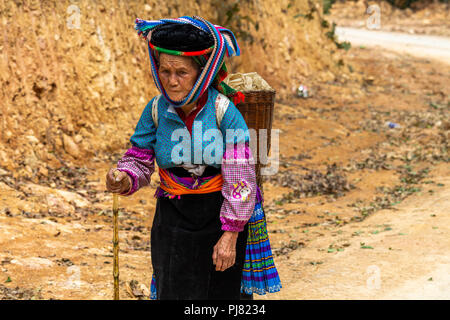 Ha Giang, Vietnam - March 18, 2018: Woman walking on a dusty road near agricultural fields in northern Vietnam - Stock Photo