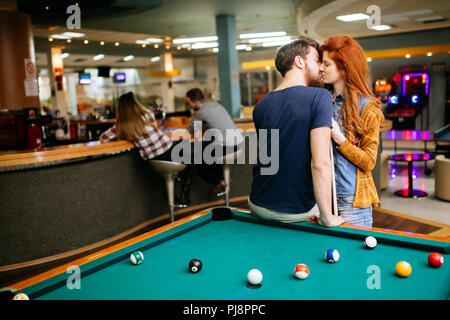 Beautiful couple kissing in billiards bar - Stock Photo