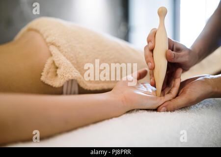 Masseur treating masseuse at modern wellness saloon - Stock Photo