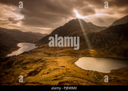 A single sunbeam pierces the clouds over Llyn Idwal, Snowdonia, North Wales - Stock Photo