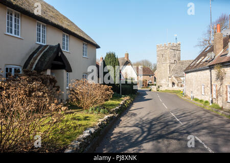 Dorchester, England, UK - February 24, 2018: Sun shines on the traditional cottages and parish church of West Stafford, near Dorchester in Dorset. - Stock Photo