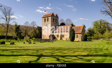 Sun shines on the tower of the 12th century Norman church of St Bartholomew in the village of Fingest, nestled under England's Chiltern Hills in Bucki - Stock Photo