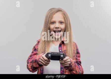 Girl with long blonde wavy hair feeling excited while playing video game - Stock Photo