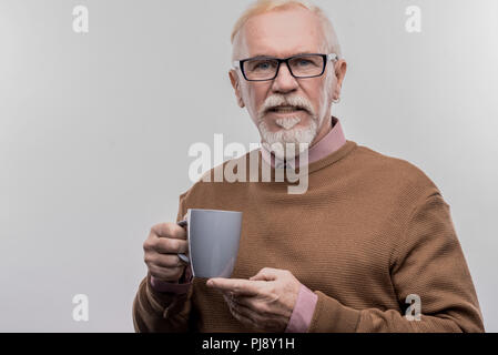Elderly businessman wearing glasses holding blue cup with hot tea - Stock Photo